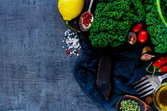 Raw vegetable ingredients. Top view of organic raw vegetable ingredients for healthy cooking or salad making with kale, lemon and tomatoes on vintage backdrop Royalty Free Stock Photo