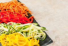 Raw vegetable noodles. Vegan food, diet. Vegetable noodles, pasta from carrot, zucchini, bell pepper. On a black slate board on a stone table. Copy space Royalty Free Stock Images
