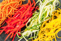 Raw vegetable noodles. Vegan food, diet. Vegetable noodles, pasta from carrot, zucchini, bell pepper. On a black slate board on a stone table. Top view  copy Stock Photo
