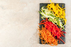 Raw vegetable noodles. Vegan food, diet. Vegetable noodles, pasta from carrot, zucchini, bell pepper. On a black slate board on a stone table. Top view  copy Royalty Free Stock Image