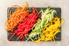Raw vegetable noodles. Vegan food, diet. Vegetable noodles, pasta from carrot, zucchini, bell pepper. On a black slate board on a stone table. Top view  copy Royalty Free Stock Photo