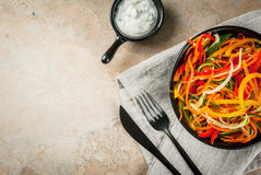 Raw vegetable noodles. Vegan food, diet. Salad from raw vegetable noodles, pasta from carrot, zucchini, bell pepper. In portioned black bowl with yogurt sauce on Stock Photo