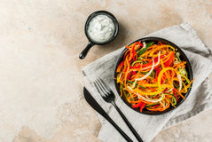 Raw vegetable noodles. Vegan food, diet. Salad from raw vegetable noodles, pasta from carrot, zucchini, bell pepper. In portioned black bowl with yogurt sauce on Royalty Free Stock Images