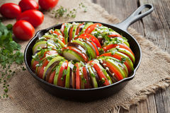 Raw vegetable ratatouille in cast iron frying pan. Preparation recipe on vintage wooden table background. Healthy organic vegan oven baked food. Rustic style Royalty Free Stock Photography