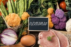 Raw vegetables, eggs and meat and text flexitarian. Closeup of a signboard with the text flexitarian on a pile of some different raw vegetables, such as stock photo