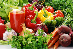 Raw vegetables and glass of juice. Freshly washed vegetables with visible drops of water and glass of vegetable juice Royalty Free Stock Photos