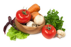 Raw vegetables over white. Fresh tomatoes , mushrooms, carrots , parsley and lettuce Royalty Free Stock Photography