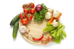 Raw vegetables on a round wooden Board Stock Photo