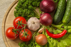 Raw vegetables on a round wooden Board. Stock Photography