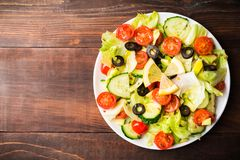Raw vegetables salad with tomato, cucumber, lettuce and avocado. On white plate over wooden table, flat lay with copy space Royalty Free Stock Photography