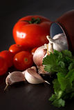 Raw vegetables on table in close-up. Close-up of garlic,tomatoes and parsley on table Royalty Free Stock Image