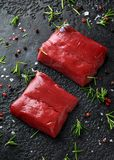 Raw venison steak with rosemary and pepper on black rustic table. royalty free stock photography