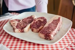 Raw wagyu beef cuts from left to right: T-Bone Steak, Rib Eye and Boneless Top Loin Steak.