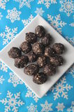 Raw walnut, chocolate and date balls on a white plate and winter background with snowflakes Royalty Free Stock Photo