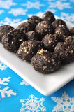 Raw walnut, chocolate and date balls on a white plate and winter background with snowflakes Stock Photos
