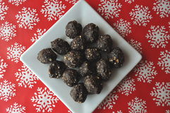 Raw walnut, chocolate and date balls on a white plate and winter background with snowflakes Stock Image