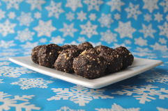 Raw walnut, chocolate and date balls on a white plate and winter background with snowflakes Royalty Free Stock Image