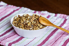 Raw walnuts in white bowl with wooden spoon on wooden table next to a red towel Stock Image
