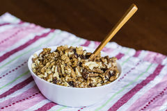 Raw walnuts in white bowl with wooden spoon on wooden table next to a red towel Royalty Free Stock Photo