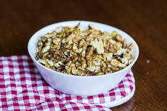 Raw walnuts in white bowl on wooden table next to a red towel Stock Photos