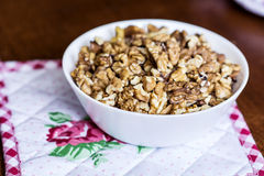 Raw walnuts in white bowl on wooden table next to a red towel Royalty Free Stock Photography