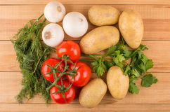 Raw washed potatoes, white onion, red tomatoes, parsley and dill Stock Images