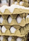 Raw eggs in carton displays for sale in a food market. Raw white eggs in carton displays for sale in a food market Royalty Free Stock Images