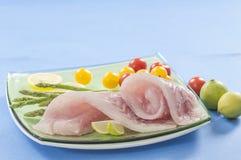 Raw white fish fillets with tomatoes and fresh oregano & Lemon slice Stock Photo