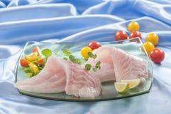 Raw white fish fillets with tomatoes and fresh oregano & Lemon slice Royalty Free Stock Photography