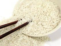 Raw white rice with chop sticks Stock Photo