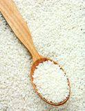 Raw white rice grain in a wooden spoon. Top view Stock Image
