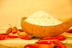 Raw white rice inside wood spoon along with red chills Stock Photos
