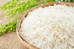 Raw white rice and wooden spoon in weave basket. Stock Images
