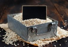 Raw White Sorghum grain in a metal box. With a small chalkboard Stock Photos