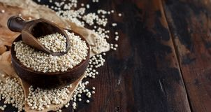 Raw White Sorghum grain. In a bowl on a wooden table stock photos