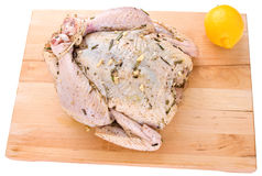 Raw whole chicken on a cutting board. With a lemon Royalty Free Stock Photos