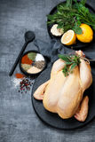Raw whole chicken, herbs, spices and lemon Royalty Free Stock Photography