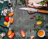 Raw whole chicken with oil and vegetables ingredients for cooking on rustic background, frame, top view. Stock Images