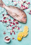 Raw whole fish on light turquoise background with ice cubes and ingredients, top view. Seafood concept. stock photo