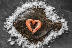 Raw whole flounder fish with shrimps stacked as a heart on ice over dark stone background. Creative layout made of fish, top view.  stock image
