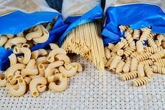 raw whole-grain pasta in bags on a wicker cloth on the table. top view royalty free stock photo