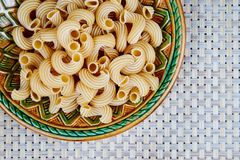 raw whole-grain pasta in a plate on a wicker cloth on the table. top view stock photo