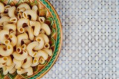 raw whole-grain pasta in a plate on a wicker cloth on the table. top view stock photography