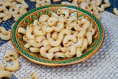 raw whole-grain pasta in a plate on a wicker cloth on the table. top view royalty free stock images