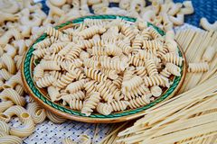 raw whole-grain pasta in a plate on a wicker cloth on the table. top view stock photos