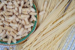 raw whole-grain pasta in a plate on a wicker cloth on the table. top view royalty free stock photos
