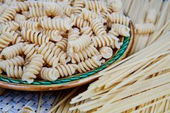 raw whole-grain pasta in a plate on a wicker cloth on the table. top view stock image