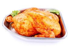 Raw whole marinated chicken in aluminum foil tray isolated Stock Image