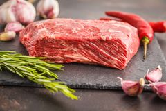 Raw whole piece of beef on slate with spices, fresh raw meat. Raw whole piece of beef on slate with spices, dark background, copy space Royalty Free Stock Photo