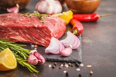 Raw whole piece of beef on slate with spices, fresh raw meat. Raw whole piece of beef on slate with spices, dark background, copy space Stock Photos